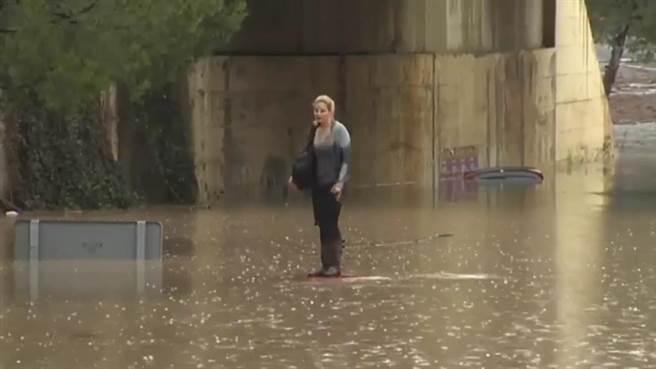 被困在水上的莎莉,就帶著她的包包爬上車頂等待救援。