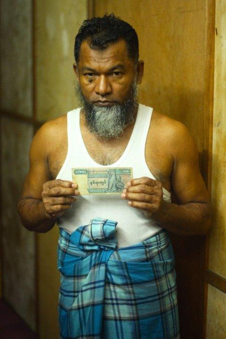 手中握著200 緬元鈔票。