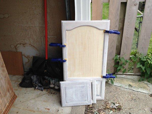 他取出了櫃門的玻璃, 填上一塊膠合板。