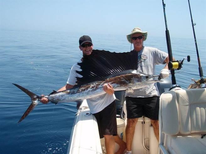 男子和友人開心地和這條魚合照留念。